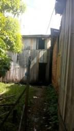 Vende se um terreno com uma casa de madeira no terreno