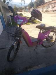 Bicicleta elétrica rosa com banco e capacete