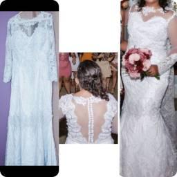 Vestido de noiva estilo sereia com  véu longo.