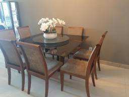 Mesa quadrada com oito cadeiras acolchoadas no assento e encosto
