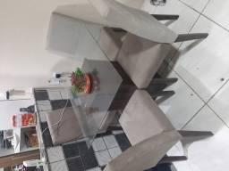Mesa de vidro com cadeiras colchoadas