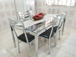 Mesa  inox  e vidro com seis cadeiras.