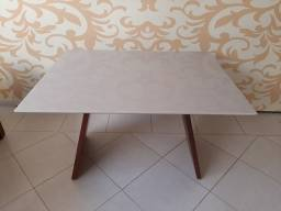 Mesa  com tampo de vidro branco.