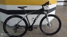 Bicicleta Caloi aro 29, com capacete e sapatilha para ciclismo.