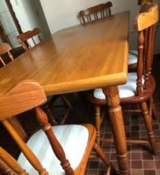 Mesa de madeira com cadeiras estofadas