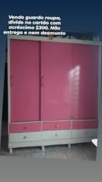 Guarda roupa rosa e branco com porta de correr