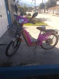 Bicicleta elétrica rosa com banco acolchoado e capacete