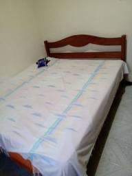 Uma cama em madeira e colchão casal
