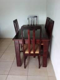Mesa com tampo de vidro e cadeiras de madeira