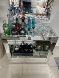 Bar aparador espelhado com diversas bebidas e espelho bisote.