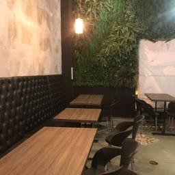 Sofá mesas cadeiras e jardim vertical
