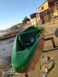 Barco baitera motor de popa e redes de pesca.