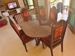 Mesa rústica estilo colonial com cadeiras.