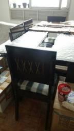 Mesa de madeira com vidro no meio e seis cadeiras