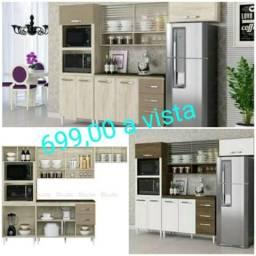 Armário de cozinha com balcão e divisórias para forno e microondas.