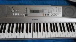 Violão com capa e um teclado psr303 com um sustain
